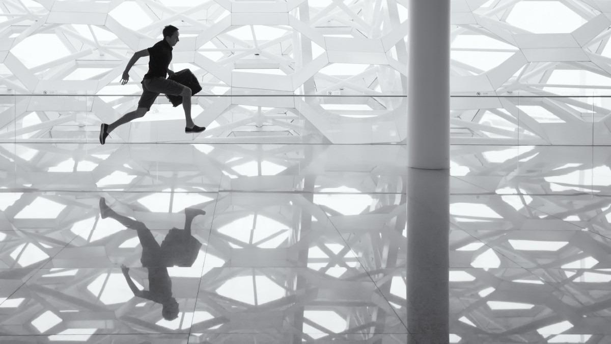Mann løper over glasstak